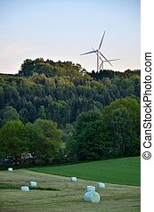Windturbines above forest and a fields- the evening in the...