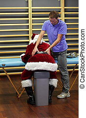 stressed Santa Claus massage - male therapist massaging...