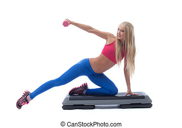 Smiling muscular girl exercising with dumbbells