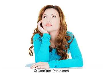 Attractive casual woman proping her head and looking up...