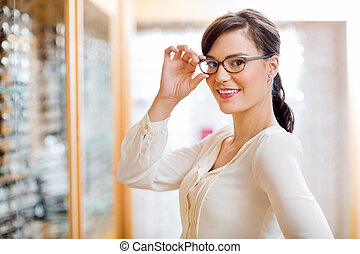 Woman Trying New Glasses In Optician Store - Portrait of...