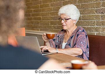 Customer Using Laptop While Having Coffee In Cafe - Senior...