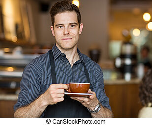 Barista with Coffee Cup - Portrait of male barista standing...