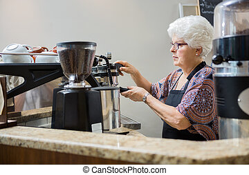 Barista Making Coffee In Cafe - Senior female barista making...