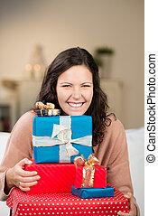 Joyful woman with a pile of Christmas gifts