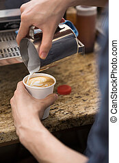Barista Making Design On Cappuccino In Coffeeshop - Cropped...