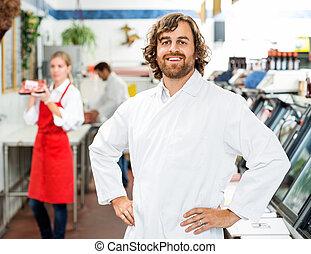 Portrait Of Confident Butcher Standing At Store - Portrait...