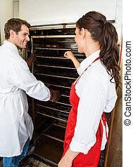 Butcher Making Beef Jerky - Male and female workers putting...