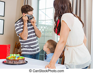 Man Taking Picture Of Family At Birthday Party