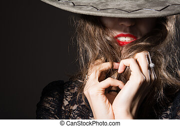 Close-up of a woman's face covered with man's hat some red...