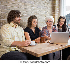 Woman With Friends Using Laptop At Cafe Table - Senior woman...