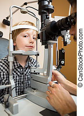 Boy Having His Eye Tested With Slit Lamp By Doctor -...