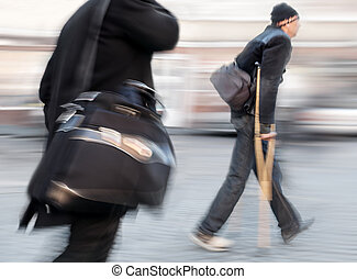 Businessman with a briefcase and a man on crutches