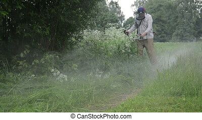 water drop wet grass cut - man with protective mask trim...