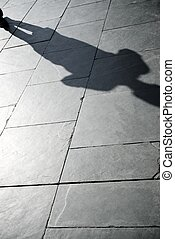 shadows of a person walking along a stone street