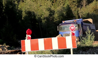 Unloading Soil at stop sign - A truck unloading its load of...
