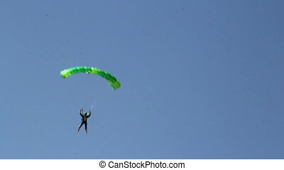 A person on the green parachute is about to land