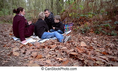 autumn picnic - family having a picnic in a forest