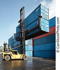 forklift lifting container - forklift is stacking two...