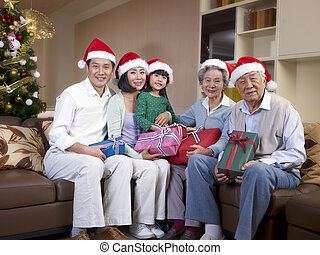 Asian Family with Christmas Hats - Home portrait of an Asian...