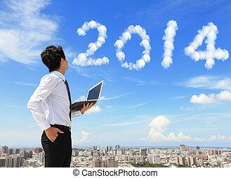 business man look to 2014 cloud - Young business man using...