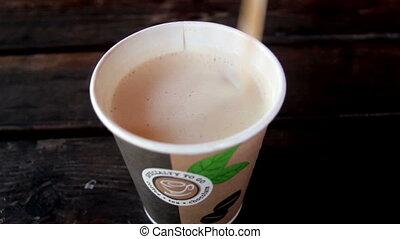 Stirring coffee in a styro cup