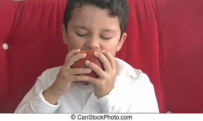 child eating red apple