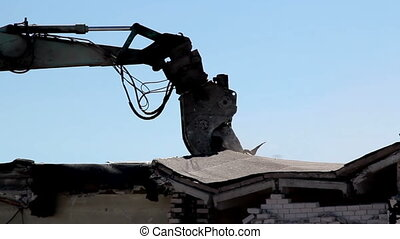 Bulldozer in action and destroying a house