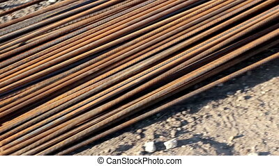 A stack of iron rods used as ma - Long rusty bars are in...