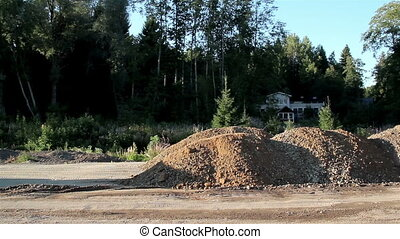 A dump truck unloading sand and gravel and house