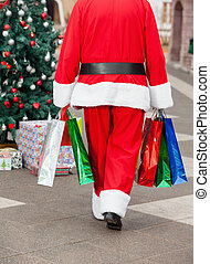 Santa Claus With Shopping Bags Walking In Courtyard - Rear...