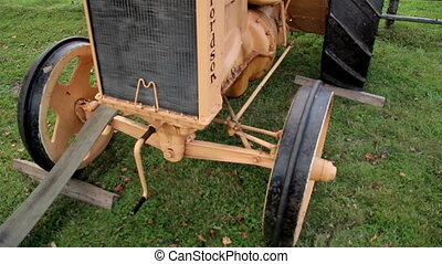 Old time antique farm tractor parking near the fence - The...