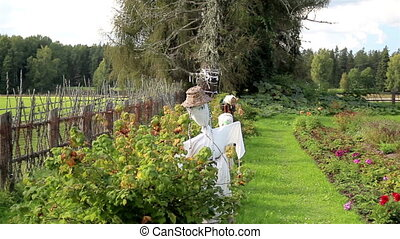 The old wooden lath fence of the ranch and the scarecrow on...