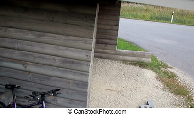 Black bitumen roof of a small log house parked bike in the...