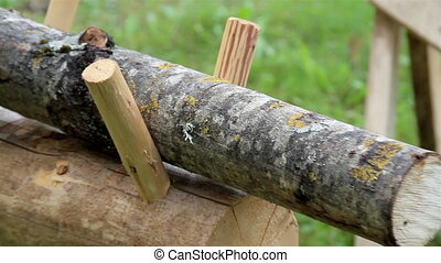 Two small logs on a wooden bench - 2 small logs topped on a...