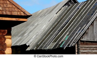Close up old damaged and new wooden shingle roof and the damaged cabin