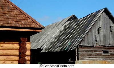 Close up old damaged and new wooden shingle roof and the damaged log house