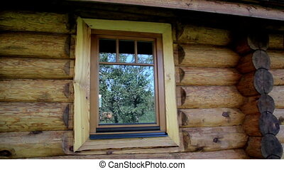 Glass window reflection on the cabin log house looks very...