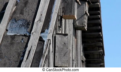 Outside wall of the cabin log house with birdhouse attached....