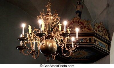 Elegant lighted chandelier hanging in church - In church the...