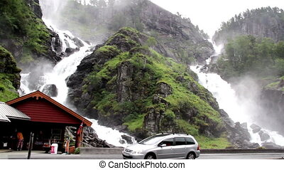 Bridge right under a beautiful water falls. Cars can pass in...