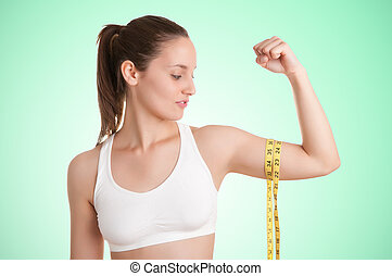 Powerful Woman - Powerful woman measuring her biceps with a...