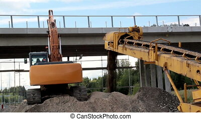 Bulldozer busy loading and unloading heaps of soil