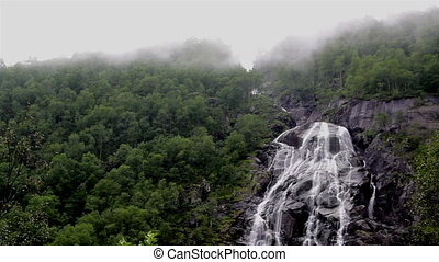 Waterfalls in a foggy mountain
