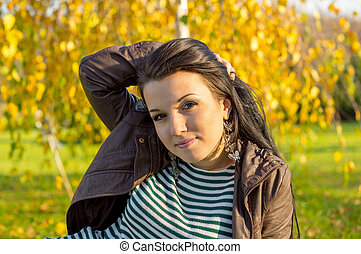 young woman laying down on the ground in autumn park