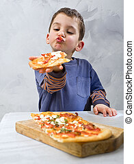 young boy eating pizza - young boy eating homemade pizza