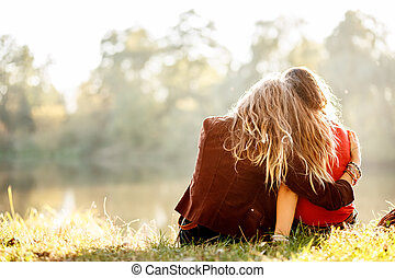 two women rear view - two young women sitting on grass...