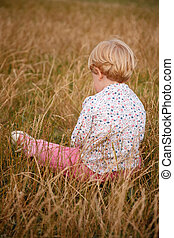 little girl rear view - little girl sitting in the field...