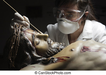 conservative restoring an image of Christ crucified on wood,...