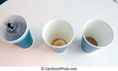 Three blue empty plastic coffee cups and a black straw -...